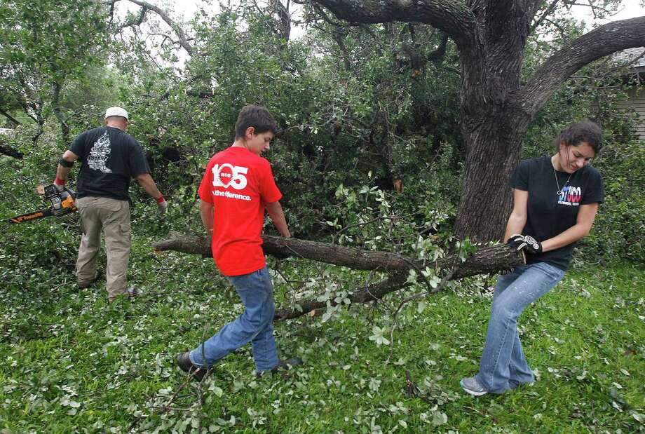 Joshua Keith, left, Alex Keith and Jordan Keith cut an oak tree in front of their home on Thursday, May 16, 2013, after a tornado destroyed part of Cleburne, Texas. A rash of tornadoes slammed into several small communities in North Texas overnight, leaving at least six people dead, dozens more injured and hundreds homeless. The violent spring storm scattered bodies, flattened homes and threw trailers onto cars.  (AP Photo/The Dallas Morning News, Michael Ainsworth)  MANDATORY CREDIT; MAGS OUT; TV OUT; INTERNET USE BY AP MEMBERS ONLY; NO SALES Photo: Michael Ainsworth, Associated Press / The Dallas Morning News