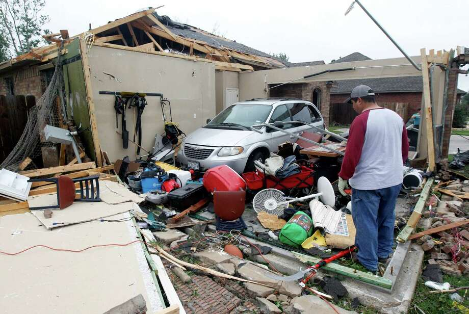 Pete Alaniz,looks for items on Thursday, May 16, 2013, to salvage after a tornado hit  his home in Cleburne, Texas. His family of four and three dogs hid in his closet while the tornado destroyed his home.   A rash of tornadoes slammed into several small communities in North Texas overnight, leaving at least six people dead, dozens more injured and hundreds homeless. The violent spring storm scattered bodies, flattened homes and threw trailers onto cars.  (AP Photo/The Dallas Morning News, Michael Ainsworth)  MANDATORY CREDIT; MAGS OUT; TV OUT; INTERNET USE BY AP MEMBERS ONLY; NO SALES Photo: Michael Ainsworth, Associated Press / The Dallas Morning News