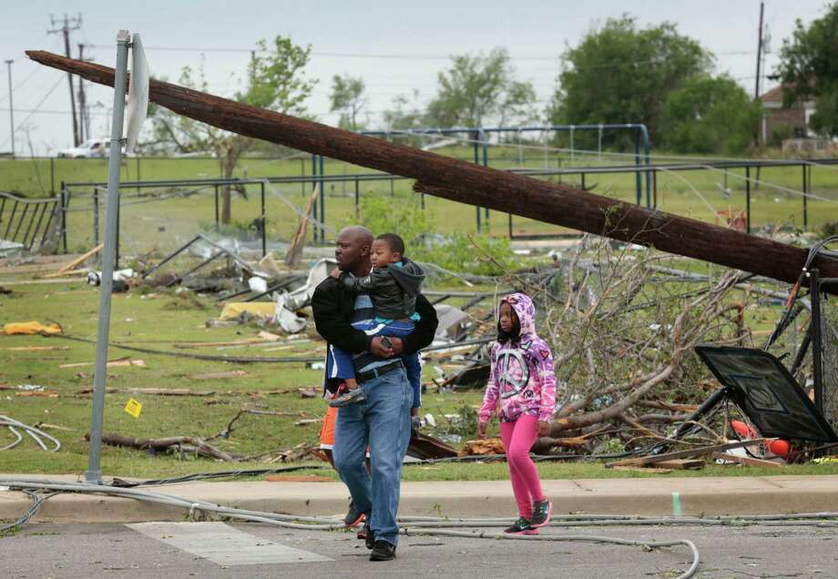 Residents tour the damage on Thursday, May 16, 2013, after a tornado destroyed part of Cleburne, Texas Wednesday night.  A rash of tornadoes slammed into several small communities in North Texas overnight, leaving at least six people dead, dozens more injured and hundreds homeless. The violent spring storm scattered bodies, flattened homes and threw trailers onto cars.  (AP Photo/The Dallas Morning News, Michael Ainsworth)  MANDATORY CREDIT; MAGS OUT; TV OUT; INTERNET USE BY AP MEMBERS ONLY; NO SALES Photo: Michael Ainsworth, Associated Press / The Dallas Morning News