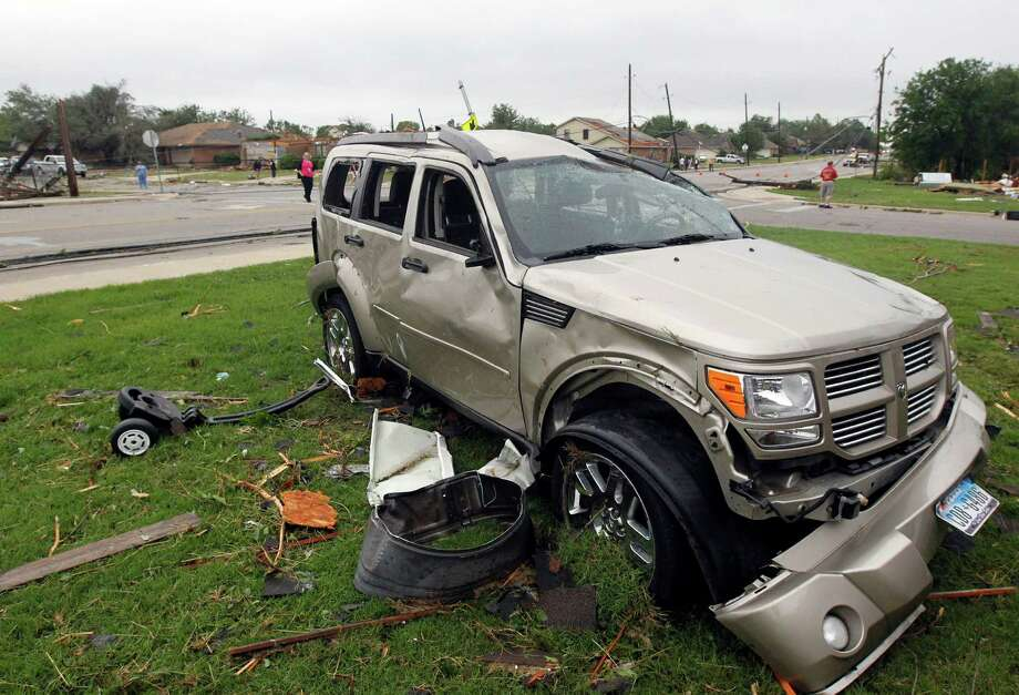 Debris surrounds a damaged vehicle on Thursday, May 16, 2013, in Cleburne, Texas.  A rash of tornadoes slammed into several small communities in North Texas overnight, leaving at least six people dead, dozens more injured and hundreds homeless. The violent spring storm scattered bodies, flattened homes and threw trailers onto cars.  (AP Photo/The Dallas Morning News, Michael Ainsworth)  MANDATORY CREDIT; MAGS OUT; TV OUT; INTERNET USE BY AP MEMBERS ONLY; NO SALES Photo: Michael Ainsworth, Associated Press / The Dallas Morning News