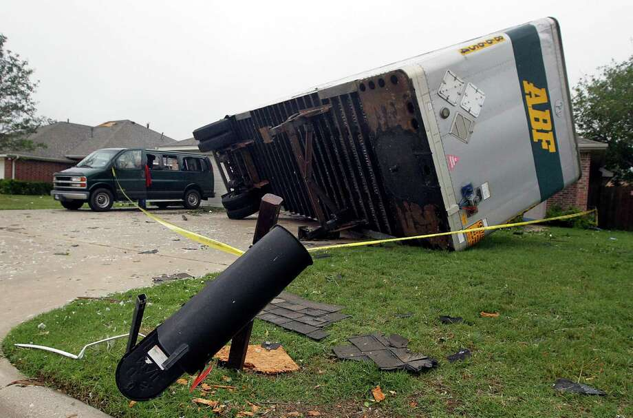 A semi trailer sits on its side, Thursday, May 16, 2013, after it was knocked onto homes after a tornado destroyed part of Cleburne, Texas late Wednesday.  A rash of tornadoes slammed into several small communities in North Texas overnight, leaving at least six people dead, dozens more injured and hundreds homeless. The violent spring storm scattered bodies, flattened homes and threw trailers onto cars.  (AP Photo/The Dallas Morning News, Michael Ainsworth)  MANDATORY CREDIT; MAGS OUT; TV OUT; INTERNET USE BY AP MEMBERS ONLY; NO SALES Photo: Michael Ainsworth, Associated Press / The Dallas Morning News