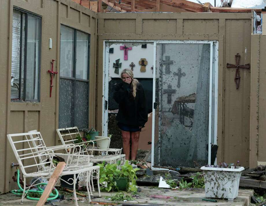 Lisa Montgomery looks over her patio, Thursday, May 16, 2013, after was destroyed by a tornado late Wednesday in Cleburne, Texas. Montgomery took shelter in her bathtub as the roof was taken off her house.  A rash of tornadoes slammed into several small communities in North Texas overnight, leaving at least six people dead, dozens more injured and hundreds homeless. The violent spring storm scattered bodies, flattened homes and threw trailers onto cars.  (AP Photo/The Dallas Morning News, Michael Ainsworth)  MANDATORY CREDIT; MAGS OUT; TV OUT; INTERNET USE BY AP MEMBERS ONLY; NO SALES Photo: Michael Ainsworth, Associated Press / The Dallas Morning News
