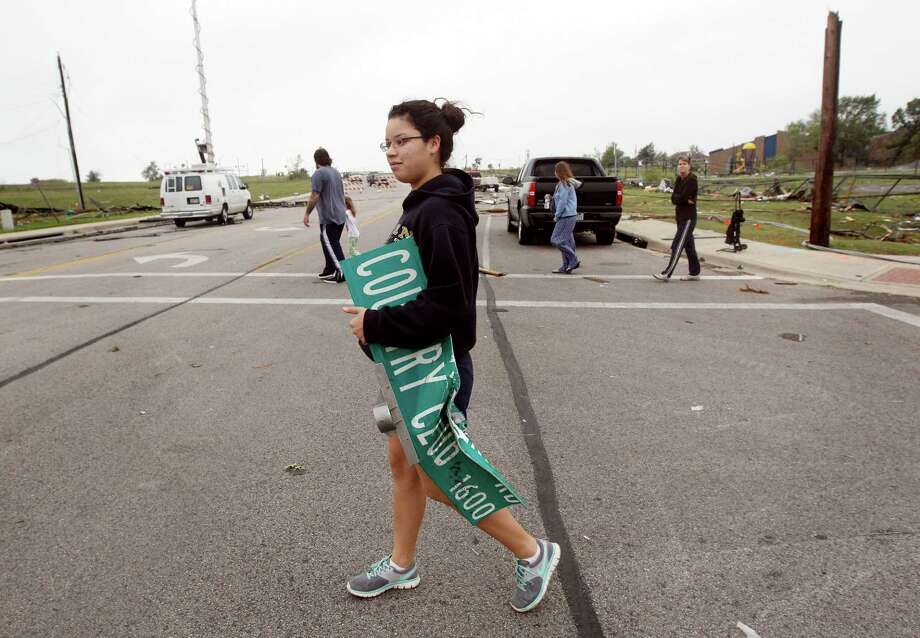 Kelly Gomez, 18, grabs a Country Club Road  street sign she found in debris, on Thursday, May 16, 2013,  after a tornado hit Cleburne, Texas late Wednesday.   A rash of tornadoes slammed into several small communities in North Texas overnight, leaving at least six people dead, dozens more injured and hundreds homeless. The violent spring storm scattered bodies, flattened homes and threw trailers onto cars.  (AP Photo/The Dallas Morning News, Michael Ainsworth)  MANDATORY CREDIT; MAGS OUT; TV OUT; INTERNET USE BY AP MEMBERS ONLY; NO SALES Photo: Michael Ainsworth, Associated Press / The Dallas Morning News