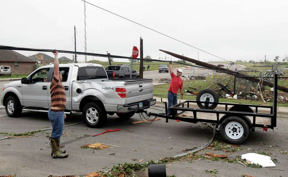 Residents raise a  downed power lines to help a motorist on Thursday, May 16, 2013, in Cleburne, Texas.  A rash of tornadoes slammed into several small communities in North Texas overnight, leaving at least six people dead, dozens more injured and hundreds homeless. The violent spring storm scattered bodies, flattened homes and threw trailers onto cars.  (AP Photo/The Dallas Morning News, Michael Ainsworth)  MANDATORY CREDIT; MAGS OUT; TV OUT; INTERNET USE BY AP MEMBERS ONLY; NO SALES Photo: Michael Ainsworth, Associated Press / The Dallas Morning News