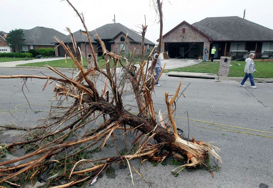 Part of a pine tree sits in the middle of the road on Thursday, May 16, 2013 in Cleburne, Texas.  A rash of tornadoes slammed into several small communities in North Texas overnight, leaving at least six people dead, dozens more injured and hundreds homeless. The violent spring storm scattered bodies, flattened homes and threw trailers onto cars.  (AP Photo/The Dallas Morning News, Michael Ainsworth)  MANDATORY CREDIT; MAGS OUT; TV OUT; INTERNET USE BY AP MEMBERS ONLY; NO SALES Photo: Michael Ainsworth, Associated Press / The Dallas Morning News