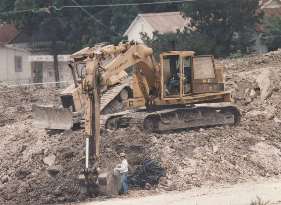 In December 1990 more than a dozen unforeseen underground storage tanks and sumps were found to have contaminated soil and water at the Alamodome site. It took 10 years, millions of dollars and several lawsuits to clean it all up. Pictured: A worker takes a dirt sample from the bucket of this backhoe during dirt removal work at the Alamodome, May 6, 1994.