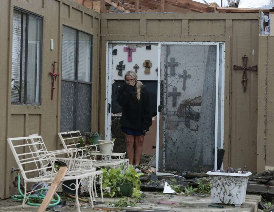 Lisa Montgomery looks over her patio, Thursday, May 16, 2013, after was destroyed by a tornado late Wednesday in Cleburne, Texas. Montgomery took shelter in her bathtub as the roof was taken off her house.  A rash of tornadoes slammed into several small communities in North Texas overnight, leaving at least six people dead, dozens more injured and hundreds homeless. The violent spring storm scattered bodies, flattened homes and threw trailers onto cars.  (AP Photo/The Dallas Morning News, Michael Ainsworth)  MANDATORY CREDIT; MAGS OUT; TV OUT; INTERNET USE BY AP MEMBERS ONLY; NO SALES