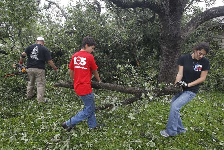 Joshua Keith, left, Alex Keith and Jordan Keith cut an oak tree in front of their home on Thursday, May 16, 2013, after a tornado destroyed part of Cleburne, Texas. A rash of tornadoes slammed into several small communities in North Texas overnight, leaving at least six people dead, dozens more injured and hundreds homeless. The violent spring storm scattered bodies, flattened homes and threw trailers onto cars.  (AP Photo/The Dallas Morning News, Michael Ainsworth)  MANDATORY CREDIT; MAGS OUT; TV OUT; INTERNET USE BY AP MEMBERS ONLY; NO SALES