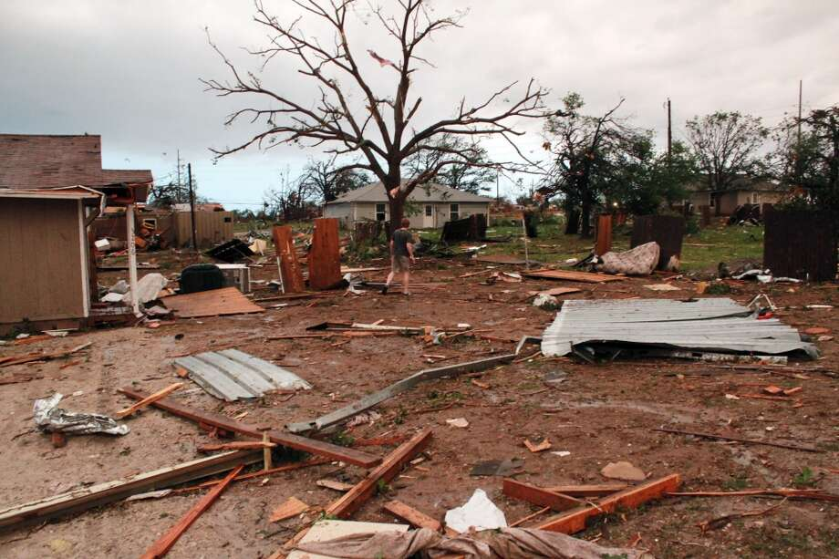 This May 16, 2013 photo provided by Nichole Tomlin shows her Granbury, Texas backyard and rubble where Tomlin says there used to be a neighborhood. A rash of tornadoes slammed into several small communities in North Texas overnight, leaving at least six people dead, dozens more injured and hundreds homeless. The violent spring storm scattered bodies, flattened homes and threw trailers onto cars.