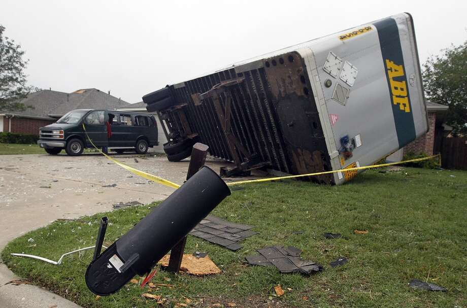 A semi trailer sits on its side, Thursday, May 16, 2013, after it was knocked onto homes after a tornado destroyed part of Cleburne, Texas late Wednesday.  A rash of tornadoes slammed into several small communities in North Texas overnight, leaving at least six people dead, dozens more injured and hundreds homeless. The violent spring storm scattered bodies, flattened homes and threw trailers onto cars.  (AP Photo/The Dallas Morning News, Michael Ainsworth)  MANDATORY CREDIT; MAGS OUT; TV OUT; INTERNET USE BY AP MEMBERS ONLY; NO SALES