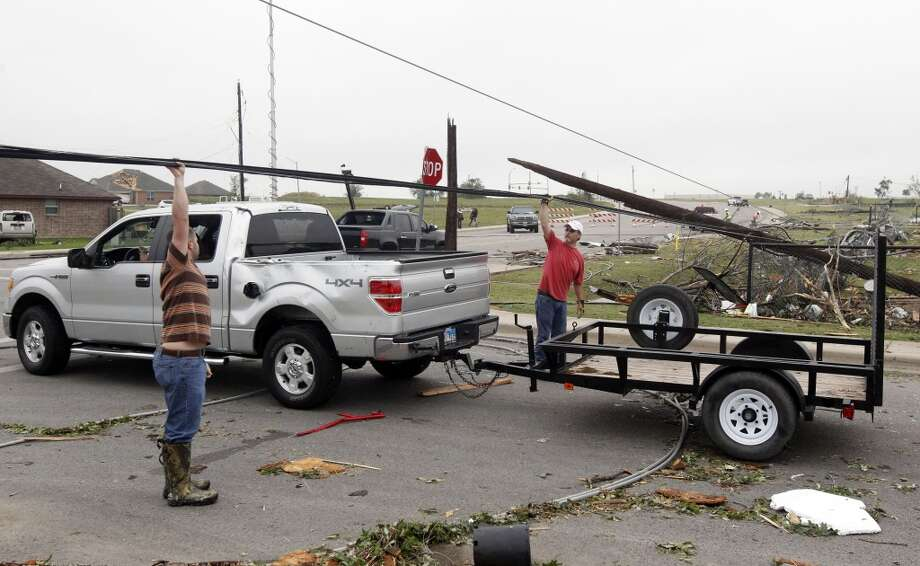 Residents raise a  downed power lines to help a motorist on Thursday, May 16, 2013, in Cleburne, Texas.  A rash of tornadoes slammed into several small communities in North Texas overnight, leaving at least six people dead, dozens more injured and hundreds homeless. The violent spring storm scattered bodies, flattened homes and threw trailers onto cars.  (AP Photo/The Dallas Morning News, Michael Ainsworth)  MANDATORY CREDIT; MAGS OUT; TV OUT; INTERNET USE BY AP MEMBERS ONLY; NO SALES