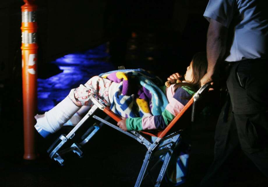 An unidentified injured young girl is wheeled to an awaiting ambulance in Granbury, Texas, on Wednesday May 15, 2013. Granby was the worst hit city as a rash of tornadoes slammed into several small communities in North Texas overnight, leaving at least six people dead, dozens more injured and hundreds homeless.  (AP Photo/Mike Fuentes)