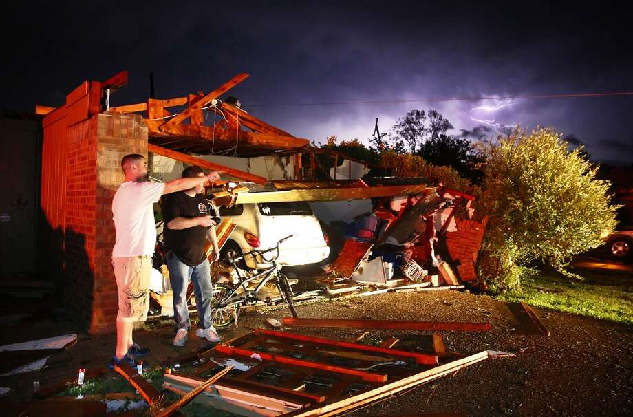 Derrek Grisham, left, points out neighborhood damage to storm chaser Travis Schafer after a tornado damaged his mother's house on Hyde Park Lane at Country Club Rd. in Cleburne, Texas,Wednesday night, May 15, 2013. Cleburne Mayor Scott Cain early Thursday declared a local disaster as schools canceled classes amid the destruction. (AP Photo/The Dallas Morning News, Tom Fox)  MANDATORY CREDIT; MAGS OUT; TV OUT; INTERNET USE BY AP MEMBERS ONLY; NO SALES