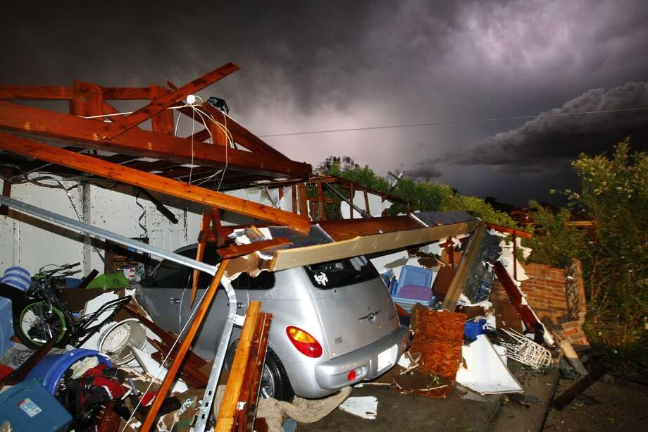 Lightning strikes from a storm illuminate a home damaged by a tornado on Hyde Park Lane at Country Club Rd. in Cleburne, Wednesday night, May 15, 2013. Cleburne Mayor Scott Cain early Thursday declared a local disaster as schools canceled classes amid the destruction. (AP Photo/The Dallas Morning News, Tom Fox)  MANDATORY CREDIT; MAGS OUT; TV OUT; INTERNET USE BY AP MEMBERS ONLY; NO SALES