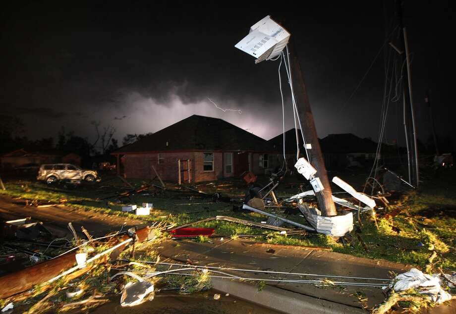 Lightning strikes from a storm illuminates the sky where damage is strewn about the street and light pole near Hyde Park Lane at Country Club Rd. after a tornado in Cleburne, Texas, Wednesday night, May 15, 2013. Cleburne Mayor Scott Cain early Thursday declared a local disaster as schools canceled classes amid the destruction. (AP Photo/The Dallas Morning News, Tom Fox)  MANDATORY CREDIT; MAGS OUT; TV OUT; INTERNET USE BY AP MEMBERS ONLY; NO SALES