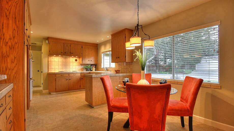 U-shaped kitchen with  tiled countertops and a dining area.