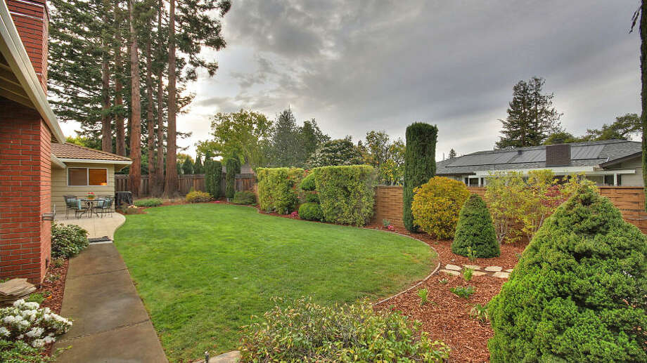 A large area featuring both a patio and rolling lawn.