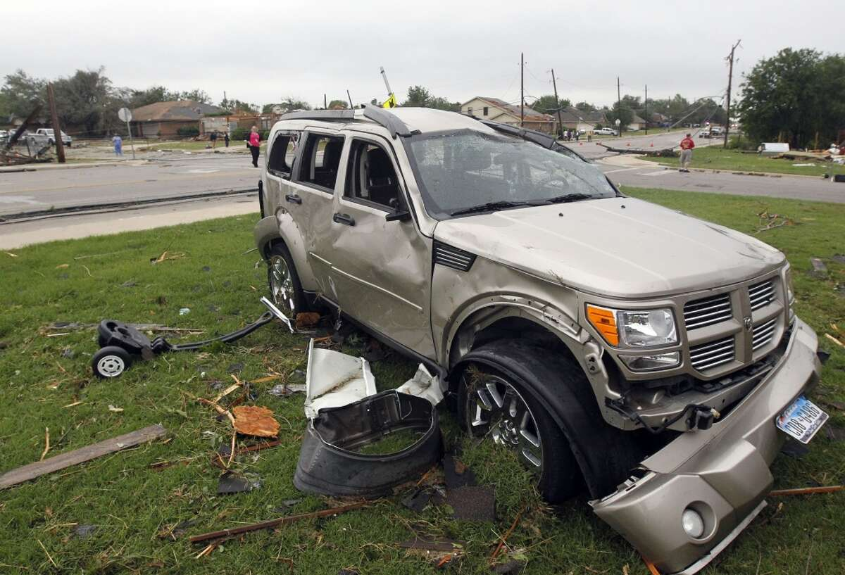 Debris surrounds a damaged vehicle on Thursday, May 16, 2013, in Cleburne, Texas. A rash of tornadoes slammed into several small communities in North Texas overnight, leaving at least six people dead, dozens more injured and hundreds homeless. The violent spring storm scattered bodies, flattened homes and threw trailers onto cars. (AP Photo/The Dallas Morning News, Michael Ainsworth)