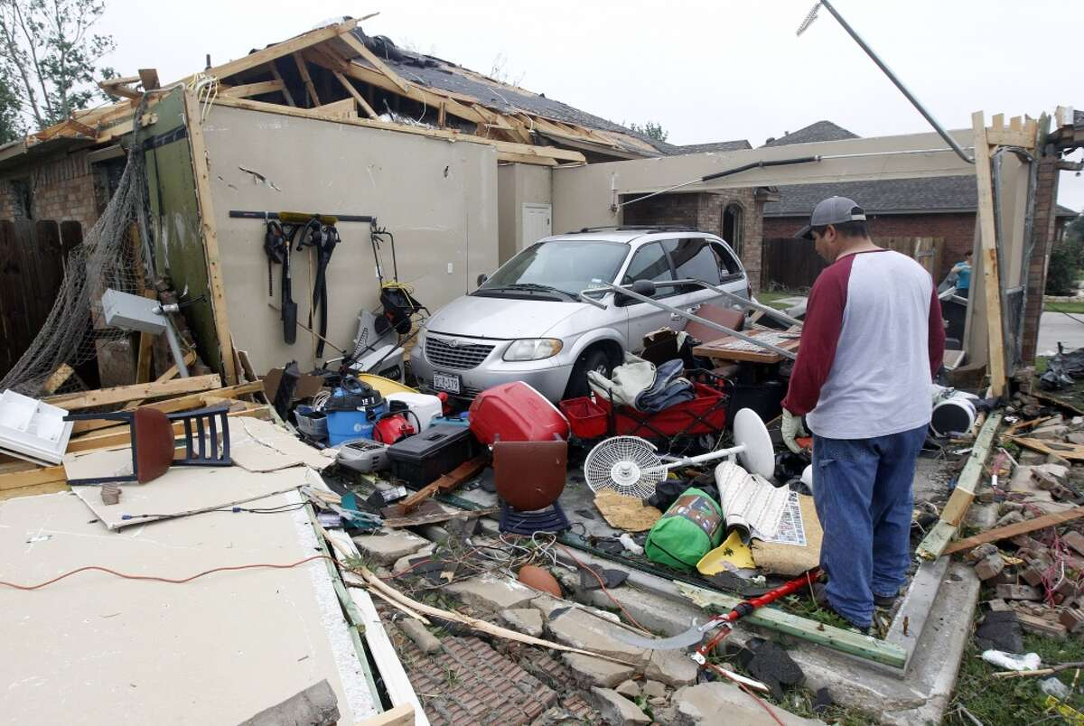 Pete Alaniz,looks for items on Thursday, May 16, 2013, to salvage after a tornado hit his home in Cleburne, Texas. His family of four and three dogs hid in his closet while the tornado destroyed his home. A rash of tornadoes slammed into several small communities in North Texas overnight, leaving at least six people dead, dozens more injured and hundreds homeless. The violent spring storm scattered bodies, flattened homes and threw trailers onto cars. (AP Photo/The Dallas Morning News, Michael Ainsworth)