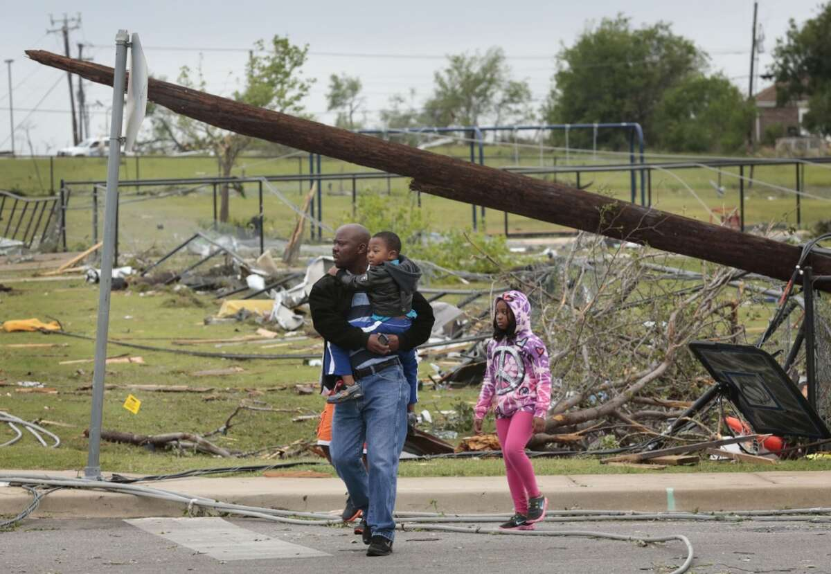 Residents tour the damage on Thursday, May 16, 2013, after a tornado destroyed part of Cleburne, Texas Wednesday night. A rash of tornadoes slammed into several small communities in North Texas overnight, leaving at least six people dead, dozens more injured and hundreds homeless. The violent spring storm scattered bodies, flattened homes and threw trailers onto cars. (AP Photo/The Dallas Morning News, Michael Ainsworth)