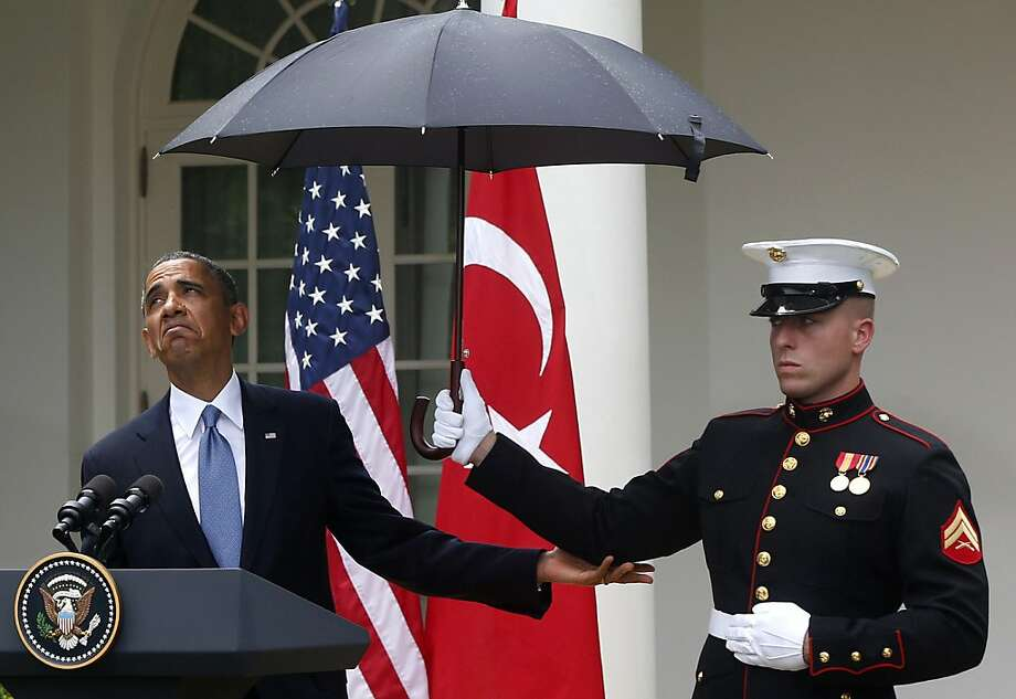 President Barack Obama looks to see if it is still raining as a Marine holds an umbrella for him during his joint news conference with Turkish Prime Minister Recep Tayyip Erdogan, not pictured, Thursday, May 16, 2013, in the Rose Garden of the White House in Washington.  Photo: Charles Dharapak, Associated Press