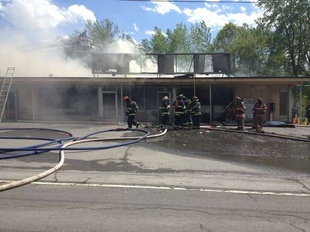 Firefighters work to douse the remaining hot spots at Handy Andy's grocery store on Watervliet Shaker Road in Colonie. (John Carl D'Annibale / Times Union)