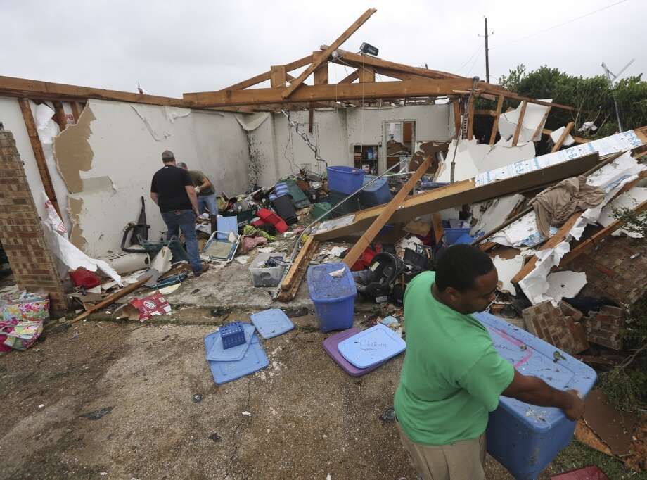 People help to start cleaning up and salvage items from a home that was destroyed by a tornado in Cleburne, Texas, Thursday, May 16, 2013. (AP Photo/LM Otero)