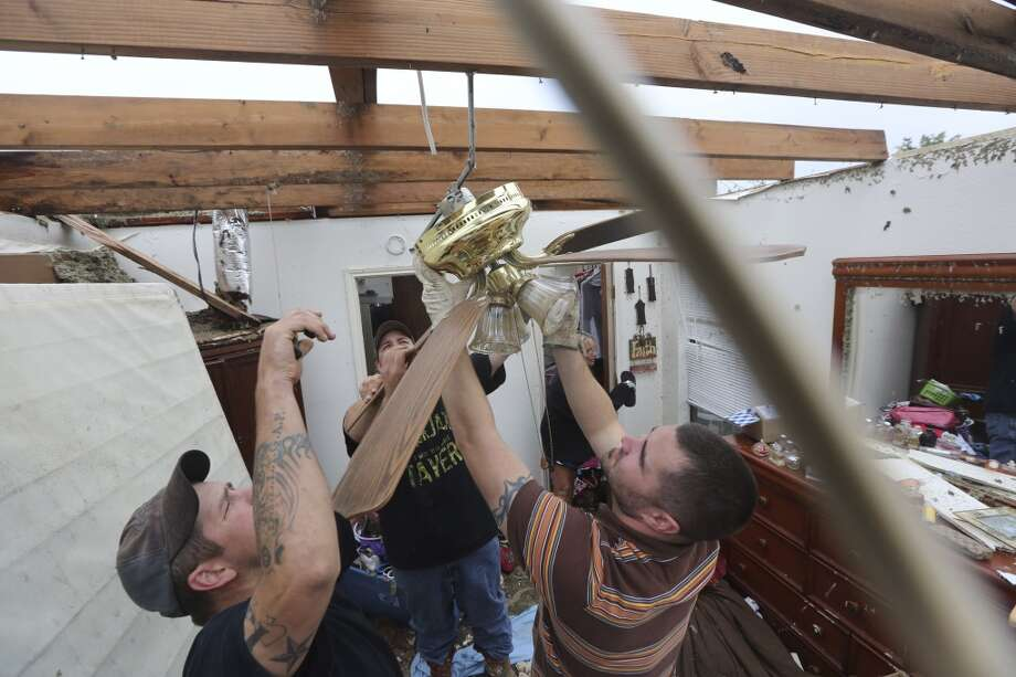 Derrek Girsham, right, Jeremy Hulce, left, and Dustin Seay cut down a fan as they start cleaning up a home that was destroyed by a tornado in Cleburne, Texas, Thursday, May 16, 2013. (AP Photo/LM Otero)