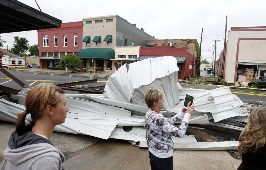 Pam House takes photos of the damage to the town from a tornado that passed the area Wednesday night, as her daughter  Melissa House looks on in downtown Ennis, Texas  on Thursday, May 16, 2013.    Forecasters say the tornado that claimed six lives and destroyed dozens of homes in northern Texas is believed to have had winds up to 200 mph (320 kph). Murphy's room is right where the tree landed.  (AP Photo/The Dallas Morning News, Vernon Bryant)  MANDATORY CREDIT; MAGS OUT; TV OUT; INTERNET USE BY AP MEMBERS ONLY; NO SALES