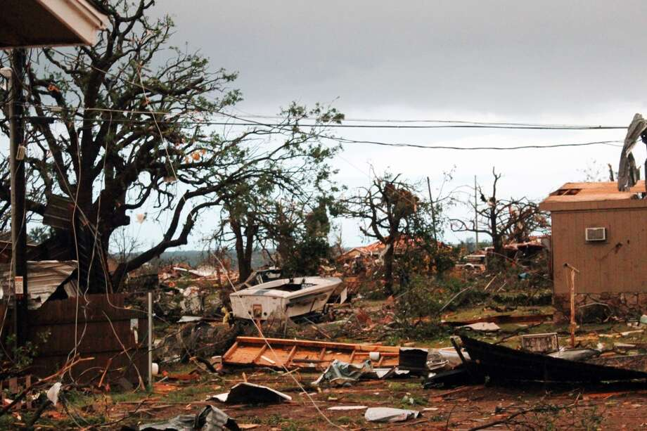 This May 16, 2013 photo provided by Nichole Tomlin shows her Granbury, Texas backyard and rubble where Tomlin says there used to be a neighborhood. A rash of tornadoes slammed into several small communities in North Texas overnight, leaving at least six people dead, dozens more injured and hundreds homeless. The violent spring storm scattered bodies, flattened homes and threw trailers onto cars. (AP Photo/Nichole Tomlin)