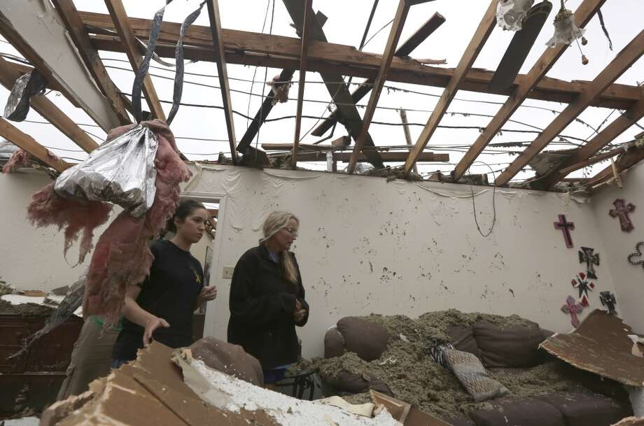 Lisa Montgomery, right, and Lauren Seay look through Montgomery's living room for items to salvage from her home that was destroyed by a tornado in Cleburne, Texas, Thursday, May 16, 2013.  Ms. Montgomery rode out the twister the night before in her bathtub with her 10-year-old son. (AP Photo/LM Otero)