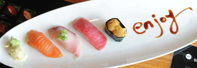 From left, three pieces of nigiri sushi sake (salmon), hamachi (yellowtail) and maguro(tuna) and uni at Sushi Na Ra on Friday, May 10, 2013 in Clifton Park, N.Y. (Lori Van Buren / Times Union) Photo: Lori Van Buren / 00022360A