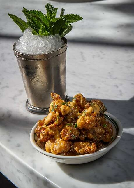 Cornmeal crusted alligator ($12) is served with the classic mint julep ($10) at Charles Phan's Hard Water at Pier 3. Photo: John Storey, Special To The Chronicle