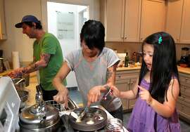 Ian Flores and Annabelle Tapacio, who own Mr. and Mrs. Miscellaneous, the popular ice cream shop in San Francisco's Dogpatch neighborhood encourage their daughter Mia 4 to help with the couple's cooking in San Francisco on Tuesday, April 30, 2013.