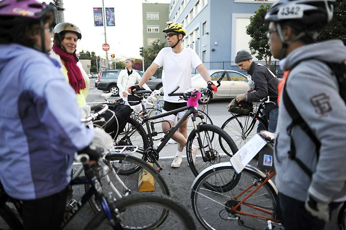 Participants in the Ride of Silence pause at the intersection of Oak and Franklin streets, where a cyclist was killed.