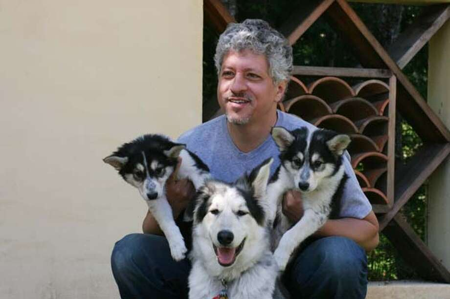 In this image provided by BioArts International, BioArts International chief executive Lou Hawthorne poses with dogs cloned from his family pet in 2008. Photo: AP / BioArts International