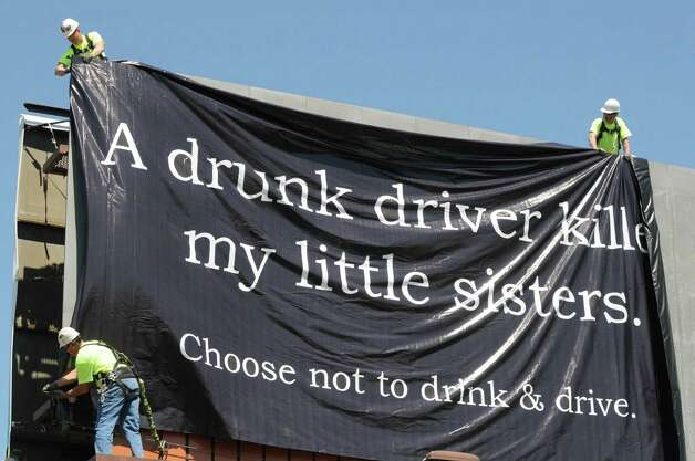 Workers from Lamar Advertising unveil a drunk driving awareness poster designed by a student from the Shenendehowa High School graphic design class, Thursday, May 16, 2013, on Route 9 in Halfmoon, N.Y. Each design class member made a poster, and one was chosen for the billboard. The winner was Liz Popson, a junior from Clifton Park, who felt that her poster would be more effective if it spoke of a close family member, such as a brother or sister. This marked the twelfth year of the event, which was backed by Lamar Advertising and Linda Campion from the Kathleen A. Campion Foundation. Saratoga County DA Jim Murphy and Chuck DeWeese ,assistant DMV commissioner for the Governor?s Safety Committee, were on hand to speak to the students. (Will Waldron/Times Union) Photo: Will Waldron
