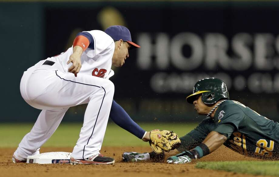 Cleveland Indians shortstop Asdrubal Cabrera, left, tags out Oakland Athletics' Yoenis Cespedes, who was trying to steal second base in the ninth inning of a baseball game Tuesday, May 7, 2013, in Cleveland.