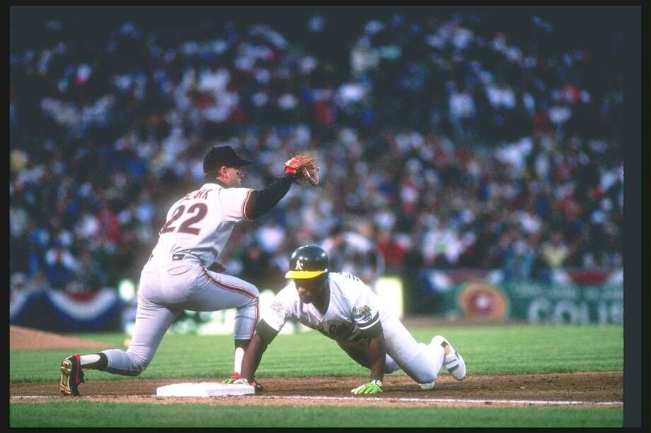 Oct 1989:  First baseman Will Clark of the San Francisco Giants tries to tag out outfielder Rickey Henderson of the Oakland Athletics during the World Series at the Oakland Coliseum in Oakland, California.