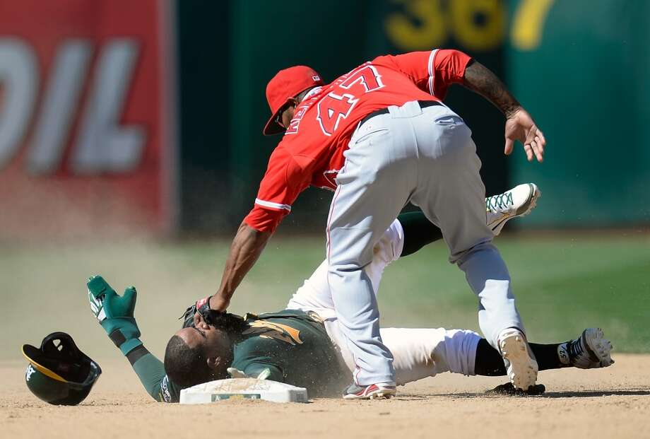 Yoenis Cespedes of the Oakland Athletics attempting to steal second base gets tagged out by Howie Kendrick #47 of the Los Angeles Angels of Anaheim.