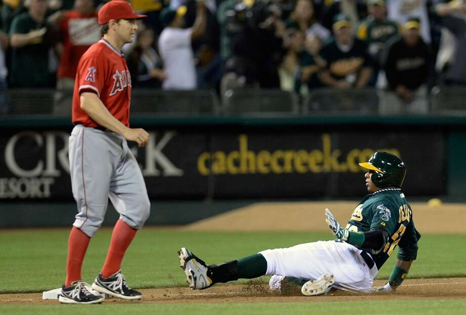 Yoenis Cespedes of the Oakland Athletics slides into third with a two-run triple.