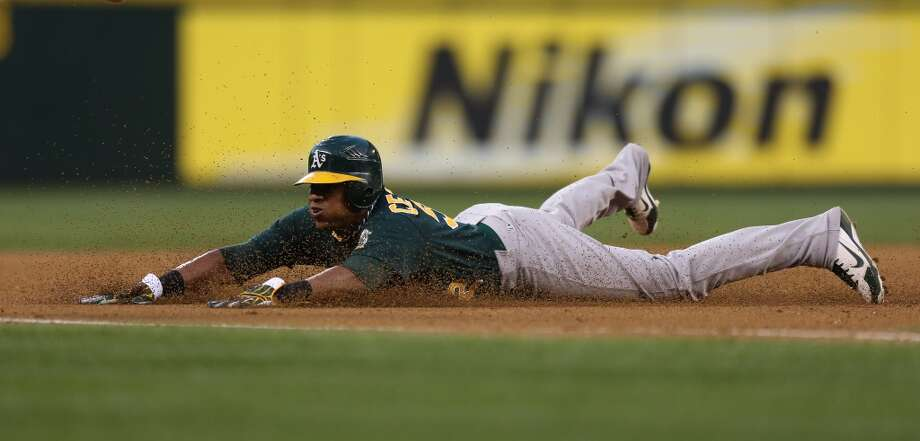 Yoenis Cespedes  steals third base in the fourth inning against the Seattle Mariners at Safeco Field on September 8, 2012 in Seattle, Washington.