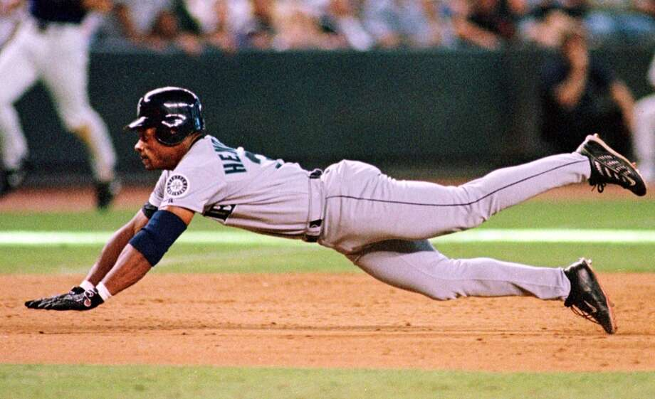 Seattle Mariners' Rickey Henderson dives for third base for a eighth inning triple against the Arizona Diamondbacks 16 July 2000 in Phoenix.