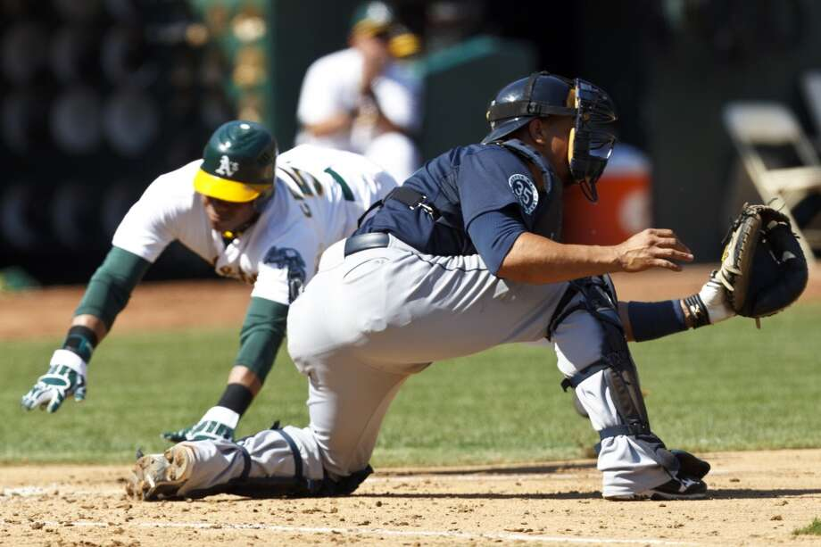 Yoenis Cespedes dives past Miguel Olivo of the Seattle Mariners to score a run during the fourth inning at O.co Coliseum on September 29, 2012.