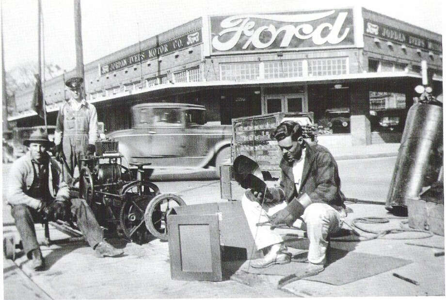 This undated photo shows streetcar repairs in front of Jordan-Ivers Motor Co. (now Jordan Ford) with Model A cars visible in the window. Photo: Photos From The Texas Transportation Museum