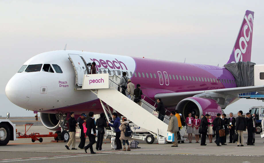 The thing we don't get about Japanese low-cost airline Peach Aviation is that its colors are pink and purple. Photo: STR, AFP/Getty Images / 2012 AFP