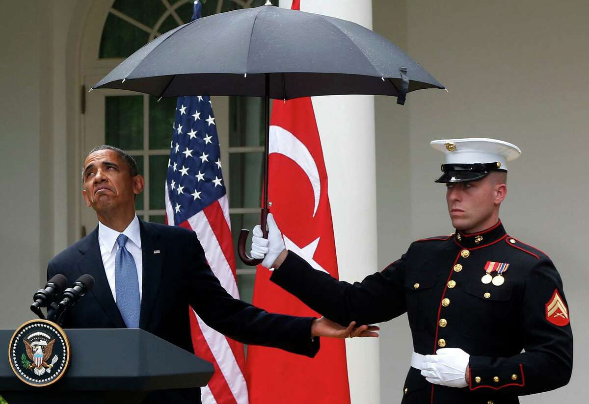 President Barack Obama looks to see if it is still raining as a Marine holds an umbrella for him during his news conference with Turkish Prime Minister Recep Tayyip Erdogan, not pictured, at the White House.