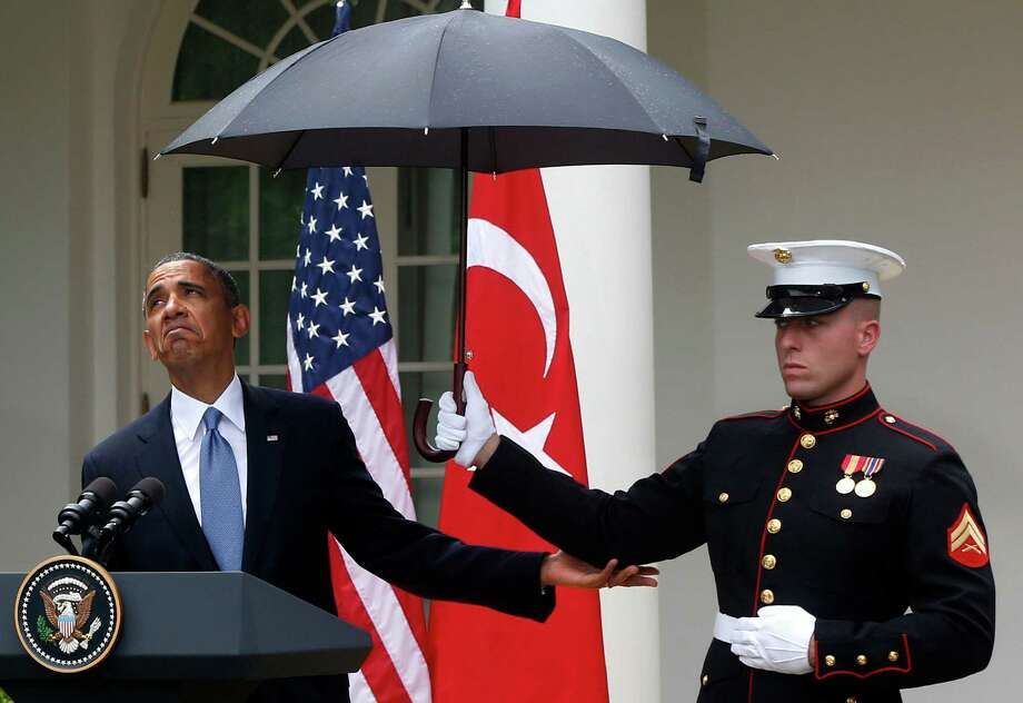President Barack Obama looks to see if it is still raining as a Marine holds an umbrella for him during his news conference with Turkish Prime Minister Recep Tayyip Erdogan, not pictured, at the White House. Photo: Charles Dharapak, STF / AP