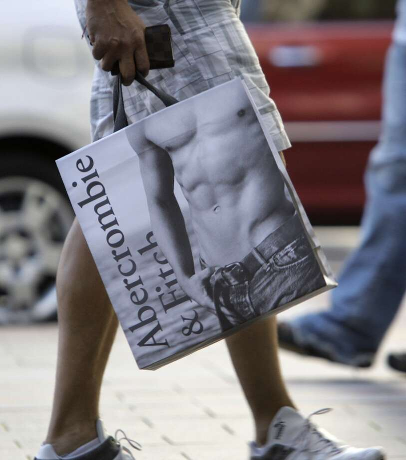 In this Oct. 6, 2009 photo, an Abercrombie & Fitch shopper walks along a sidewalk in downtown Seattle. A late Labor Day and delayed school openings offered some relief to merchants in September, helping to boost sales above Wall Street expectations. (AP Photo/Elaine Thompson)