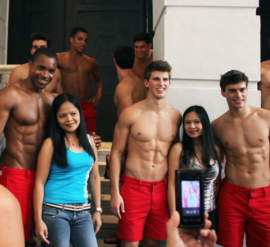 Filipino women pose for photographs with topless male models outside the soon to open Abercrombie & Fitch flagship clothing store in Hong Kong on August 5, 2012. The store is due to be opened for trading on August 11.    AFP PHOTO / LAURENT FIEVETLAURENT FIEVET/AFP/GettyImages